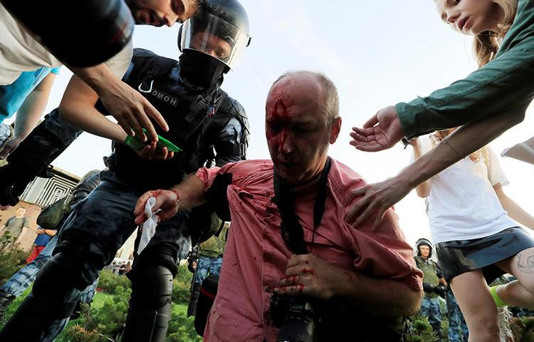 People help a wounded man during a rally calling for opposition candidates to be registered for elections to the Moscow City Duma, the capital's regional parliament, in Moscow, Russia, on July 27, 2019. Police in Moscow attacked, threatened, and detained journalists covering protests in Moscow on July 27 and August 3. (Reuters/Tatyana Makeyeva)