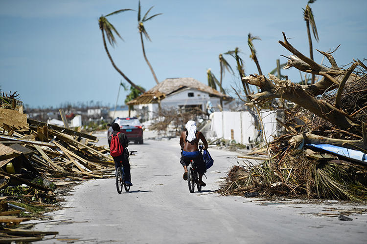 Residents pass damage caused by Hurricane Dorian on September 5, 2019, in Marsh Harbour, Great Abaco Island in the Bahamas. (AFP/Brendan Smialowski)