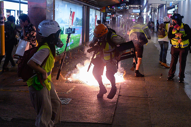 Journalists react as police fire tear gas in Hong Kong on September 8, 2019. Police recently fired tear gas and pepper spray at several groups of journalists covering protests in the city. (AFP/Philip Fong)