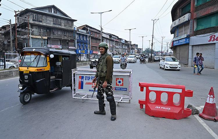 An Indian paramilitary trooper stands guard on a road in Srinagar, Kashmir's largest city, on September 7, 2019. Since the government stripped the region of its limited autonomous status and imposed a communication blackout in early August, Kashmir's news media has faced a deep existential crisis. (AFP/Tauseef Mustafa)