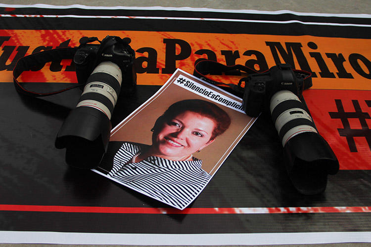 Cameras and a photo of Miroslava Breach are laid out as part of a tribute to the journalist on the second anniversary of her murder. Mexico's investigation into her killing is flawed, a report on the journalist has found. (AFP/Herika Martinez)