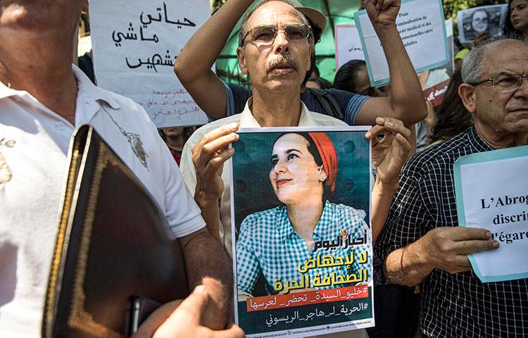 A demonstrator holds up a sign showing the portrait of Hajar Raissouni, a Morrocan journalist of the daily newspaper Akhbar El-Youm, during a protest outside a courthouse in the capital, Rabat, on September 9, 2019. (AFP/Fadel Senna)