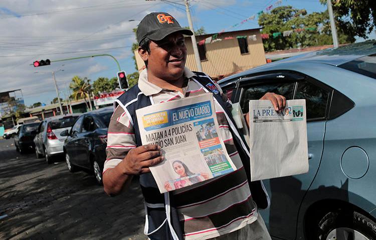 """Un vendedor de periódicos vende """"La Prensa"""" y 'El Nuevo Diario"""" el 18 de enero de 2019. Autoridades aduaneras han retenido tinta e papel de prensa para ambos diarios desde agosto de 2018. (AFP/Inti Ocon)"""