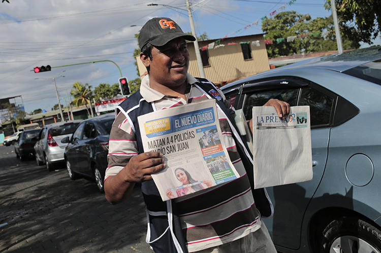"A newspaper vendor sells ""La Prensa"" and ""El Nuevo Diario"" on January 18, 2019. Customs authorities have withheld ink and newsprint supplies from both papers since August 2018. (AFP/Inti Ocon)"