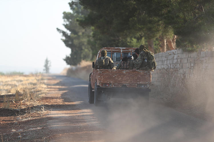 Fighters from Hayat Tahrir al-Sham are seen on the border between Hama and Idlib provinces, in Syria, on July 11, 2019. Militants from the group recently abducted journalist Ahmed Rahal in Idlib. (AFP/Omar Haj Kadour)
