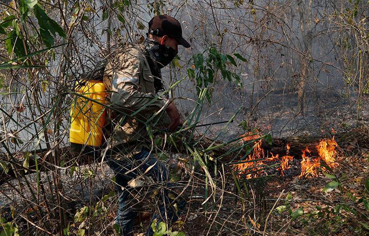 Un voluntario se esfuerza por apagar un incendio forestal en Quitunuquina, en las afueras de Robore, Bolivia, el 24 de agosto de 2019. Los incendios forestales de Bolivia han puesto al descubierto los numerosos riesgos que enfrentan los periodistas ambientales. (AP Photo/Juan Karita)