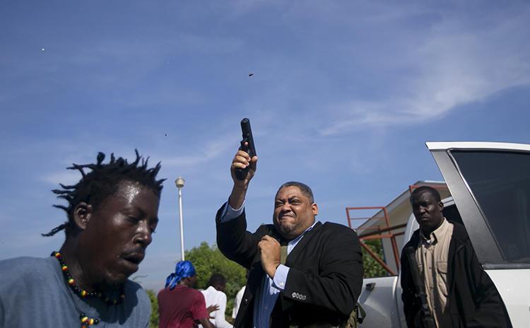 Le Sénateur Jean Marie Ralph Féthière fait feu avec son arme à Port-au-Prince, Haïti, le 23 septembre 2019. Le photographe de l'AP Chery Dieu-Nalio a été blessé par le tir au cours de l'incident. (AP/Chery Dieu-Nalio)