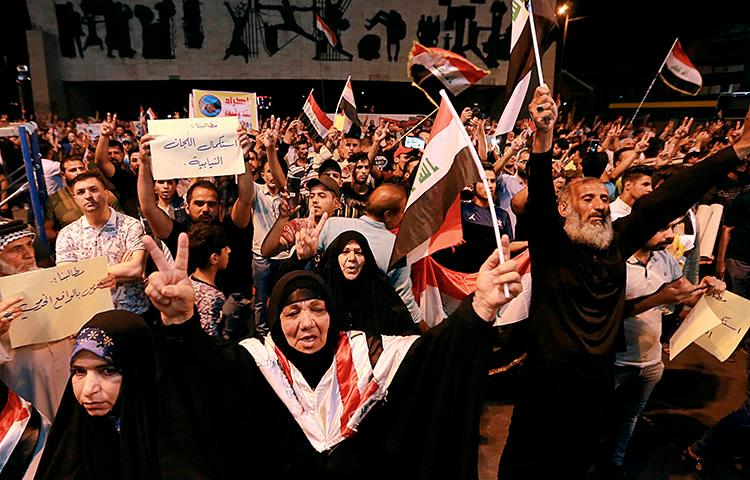 Iraqi protesters chant slogans during a demonstration in Tahrir Square in central Baghdad, Iraq, on June 21, 2019. Iraq suspended U.S.-funded broadcaster Al-Hurrah for 3 months over a corruption report on September 2. (AP Photo/Hadi Mizban)