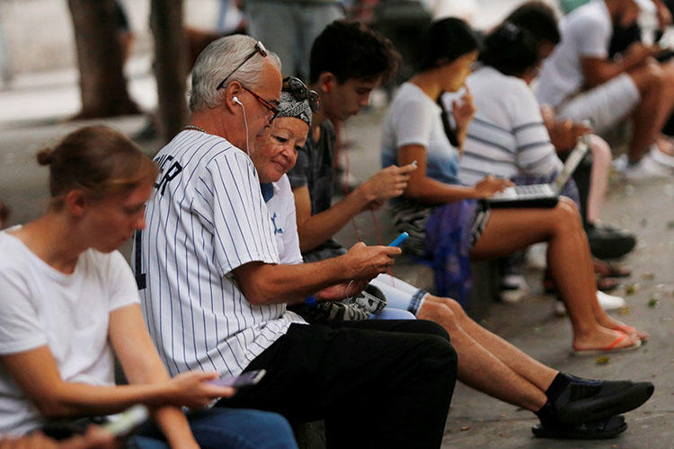 Personas usan internet en un hot-spot en La Habana, Cuba, en diciembre de 2018. Periodistas y blogeros dicen que recientes regulaciones de internet podrían legitimar la censura. (REUTERS/Stringer)