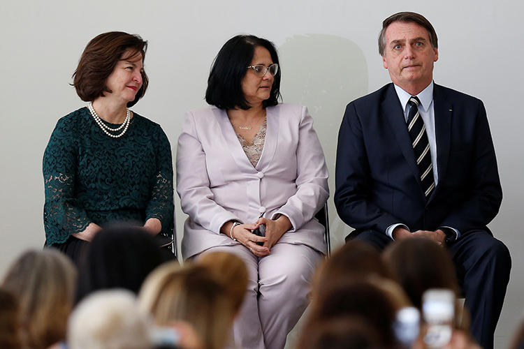 Damares Alves, Brazil's minister for women, family, and human rights (center) is seen with then Brazilian Prosecutor General Raquel Dodge and President Jair Bolsonaro in Brasilia on March 8, 2019. Alves recently filed a complaint against online outlet AzMina. (Reuters/Adriano Machado)