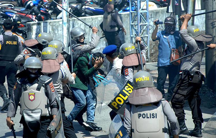 Police beat students in Makassar, Indonesia, on September 24, 2019. Several journalists were injured by police while covering the student protests. (Antara Foto/Abriawan Abhe via Reuters)