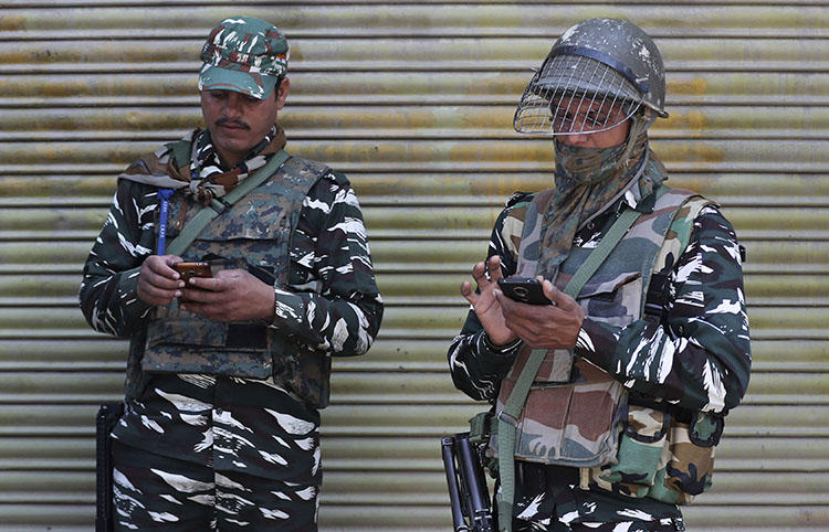 Indian paramilitary soldiers use their cellphones in Srinagar, Indian controlled Kashmir, on October 14, 2019 after the partial lifting of a communications lockdown in place since India's government downgraded the region's semi-autonomy in August. (AP Photo/Mukhtar Khan)