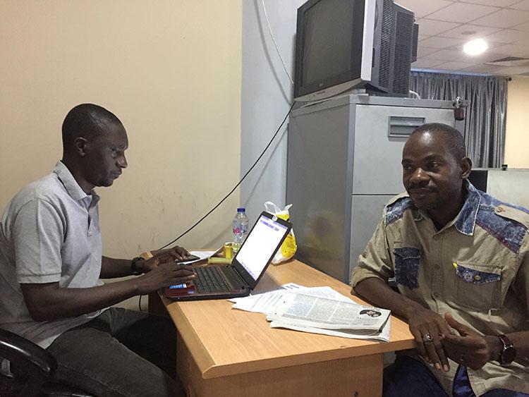 Hamza Idris (à gauche), rédacteur en chef du journal Daily Trust, est assis en février 2019 avec son collègue Hussaini Garba Mohammed dans leur bureau à Abuja, la capitale nigériane. Le bureau a été perquisitionné en janvier par l'armée, qui a saisi 24 ordinateurs. (CPJ / Jonathan Rozen)