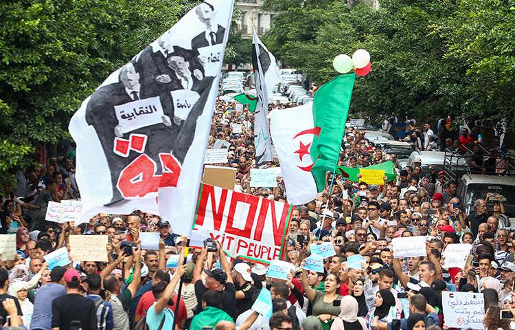 Algerian demonstrators chant and wave their country's national flag as they take part in an anti-government protest in the capital Algiers on October 15, 2019. Authorities have detained at least three more journalists in recent days. (AFP)