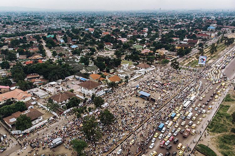 Vue aérienne de la foule rassemblée à l'extérieur du siège de l'Union pour la démocratie et le progrès social  (UDPS) à Kinshasa le 30 mai 2019, alors que les partisans attendent le retour des dépouilles de l'ancien premier ministre congolais et du leader de l'opposition Etienne Tshisekedi, morts en Belgique en  2017. Un journaliste radio congolais a été attaqué par des partisans de l'UDPS lors d'un rallye à Kinshasa le 5 octobre  2019. (AFP/Alexis Huguet)