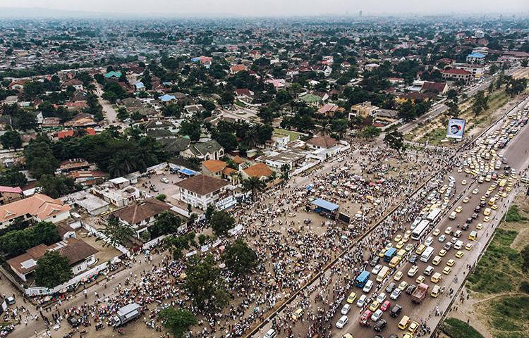 An aerial view shows a crowd gathered outside the Union for Democracy and Social Progress (UDPS) headquarters in Kinshasa on May 30, 2019, as supporters await the return of the remains of former Congolese Prime Minister and opposition leader Etienne Tshisekedi, who died in Belgium in 2017. A Congolese radio journalist was attacked by UDPS supporters at a Kinshasa rally on October 5, 2019. (AFP/Alexis Huguet)