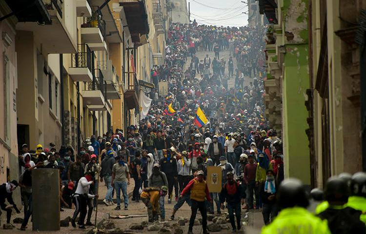 Manifestantes se enfrentan con la policía antidisturbios en Quito, mientras miles marchan contra la decisión del presidente ecuatoriano, Lenín Moreno, de recortar los subsidios al combustible, el 9 de octubre de 2019. Tanto las autoridades como los manifestantes han atacado a la prensa en medio de las protestas. (AFP/Rodrigo Buendia)