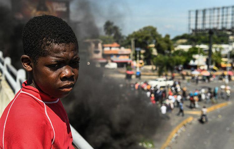 A boy looks on as protesters demand the resignation of President Jovenel Moïse in Port-au-Prince, on October 4. A radio journalist who had been critical of the unrest and who was threatened over his reporting, was killed Mirebalais in October. (AFP/Chandan Khanna)