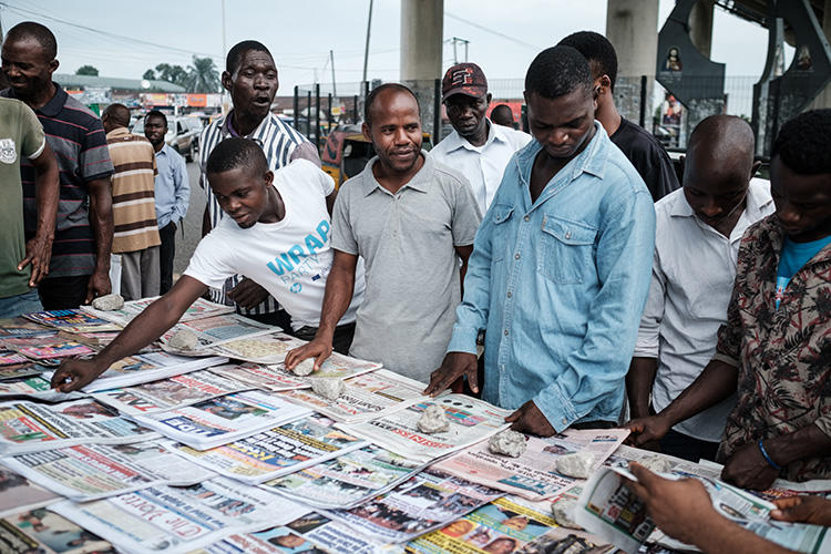 People look at front pages at a newspaper stand in Port Harcourt, after Nigeria's presidential election results were announced on February 27, 2019. Nigerian police beat two Inspiration FM journalists after covering a protest in Uyo, in Akwa-Ibom State, on September 24, 2019. (AFP/Yasuyoshi Chiba)