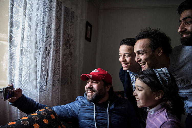 The Egyptian photojournalist Mahmoud Abu Zeid, second right, known as Shawkan, poses for a selfie at his home in Cairo on March 4, 2019. As part of the restrictive terms of his release from prison, the journalist has to spend each night at a police station. (AFP/Khaled Desouki)