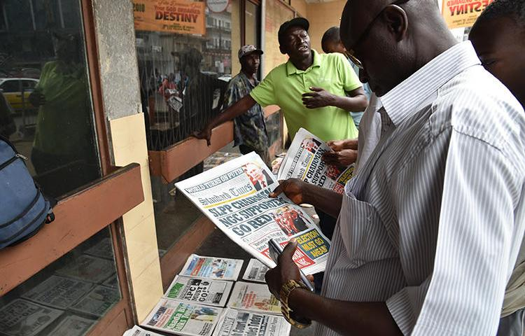 A man reads headlines of a daily newspaper on March 27, 2018, in Freetown. A freelance journalist was charged with criminal defamation in Sierra Leone in September 2019. (AFP/Issouf Sanogo)