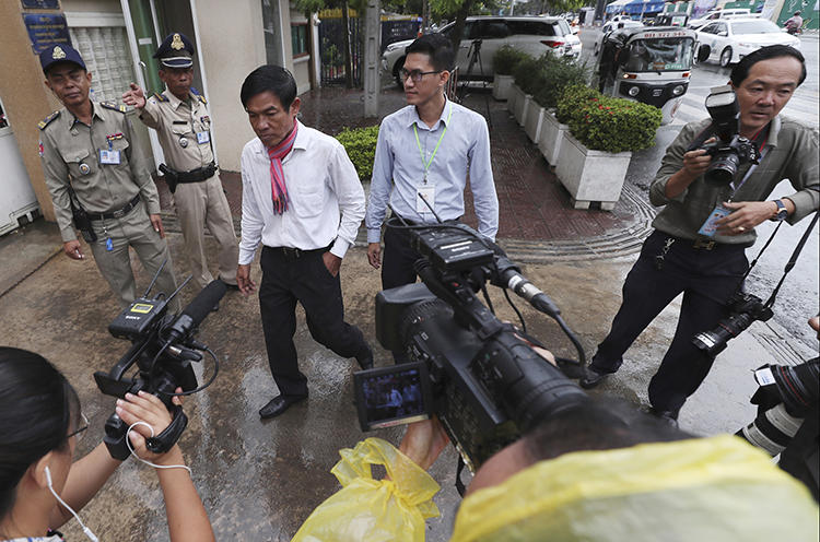 Journalists Uon Chhin, center left, and Yeang Sothearin, center right, are seen at the municipal court in Phnom Penh, Cambodia, on August 30, 2019. A municipal court judge recently ordered their case to be reinvestigated. (AP/Heng Sinith)