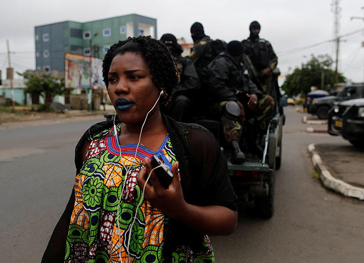 A woman walks past Rapid Intervention Battalion members as they patrol in the city of Buea in October 2018. CPJ and others are calling on the ACHPR to address human rights violations in Cameroon's Anglophone regions. (Reuters/Zohra Bensemra)
