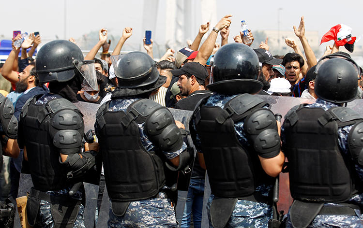 Security forces and protesters are seen in Baghdad, Iraq, on October 2, 2019. Security forces have harassed reporters covering the protests, and authorities recently cut internet access to much of the country. (Reuters/Khalid al-Mousily)