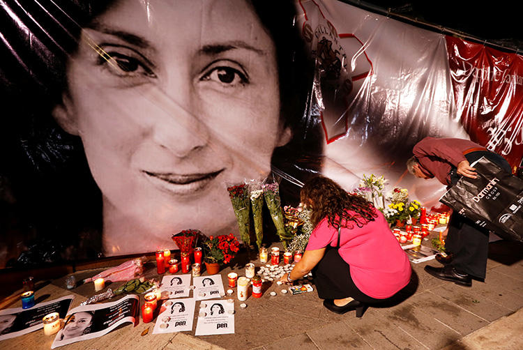 People lay flowers and candles at a memorial during a vigil and protest on the first anniversary of the assassination of journalist Daphne Caruana Galizia outside the Courts of Justice in Valletta, Malta, on October 16, 2018. On the second anniversary of her murder, CPJ joined a call to end impunity in her case. (Reuters/Darrin Zammit Lupi)