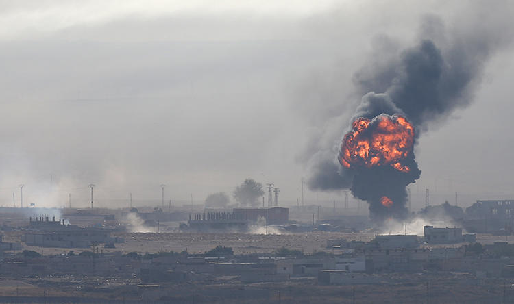 An explosion is seen over the Syrian town of Ras al-Ain on October 12, 2019. Turkish airstrikes near Ras al-Ain recently killed two journalists. (Reuters/Stoyan Nenov)