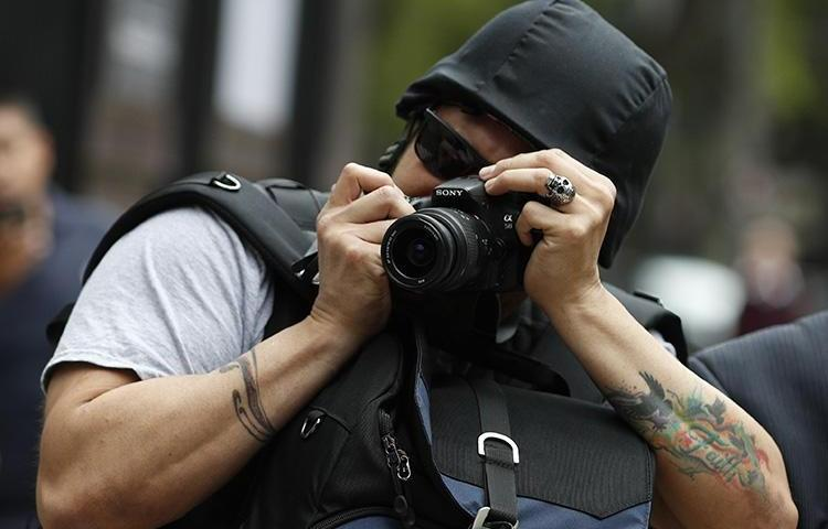 A photographer takes pictures of a protest against the murder and disappearances of journalists in Mexico, in Mexico City on August 21, 2019. (AP/Rebecca Blackwell)