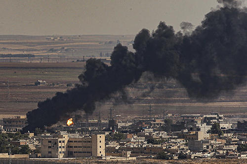 Smoke is seen billowing from the sites of airstrikes in Ras al-Ayn, Syria, on October 13, 2019. Two Syrian Kurdish journalists were killed in the attacks. (AP/Emrah Gurel)