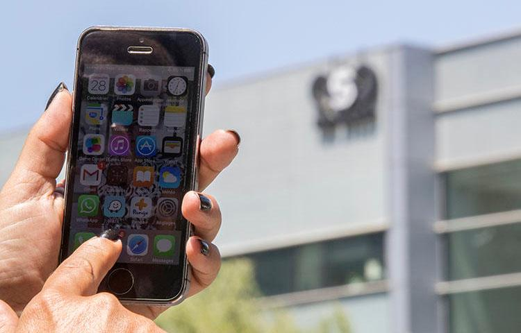 An Israeli woman uses her iPhone in front of the building housing the Israeli NSO group, on August 28, 2016, in Herzliya, near Tel Aviv. NSO Group has been accused of facilitating surveillance of journalists through sales of its Pegasus spyware. (AFP/Jack Guez)