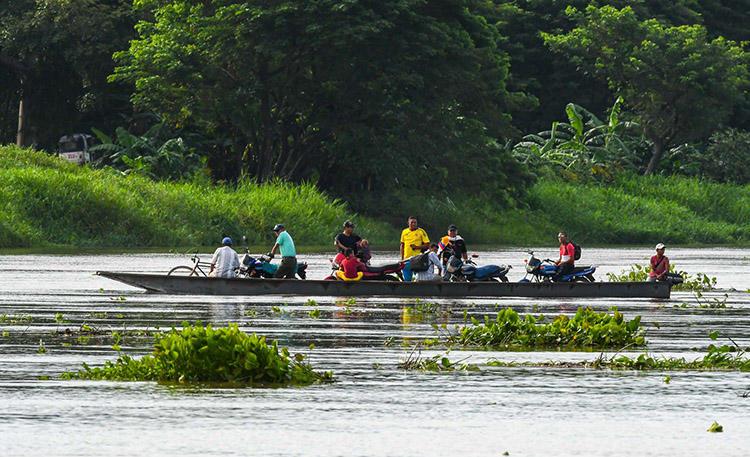 Un grupo de personas transportan motocicletas en una lancha por el río Magdalena en Santa Cruz de Mompox, Colombia, en septiembre de 2017. Atacantes prendieron fuego a una lancha que un periodista en Simití utilizaba para informar sobre comunidades remotas a lo largo del río. (AFP / Luis Acosta)