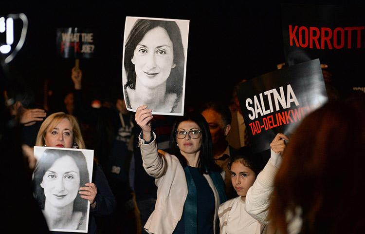 Protesters hold up placards and pictures of the murdered Maltese blogger Daphne Caruana Galizia as they gather outside the prime minister's office in Valletta, Malta, on November 20, 2019. CPJ and other press freedom groups are reiterating their call for an independent investigation into the journalist's killing. (AFP/Matthew Mirabelli)