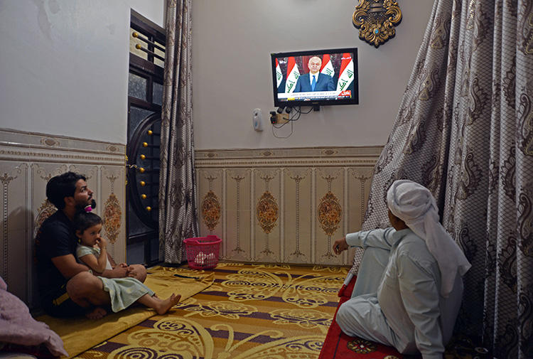 People watch television in Najaf, Iraq, on October 31, 2019. Iraq's media regulator recently ordered the closure of 12 broadcast outlets throughout the country. (AFP/Haidar Hamdani)