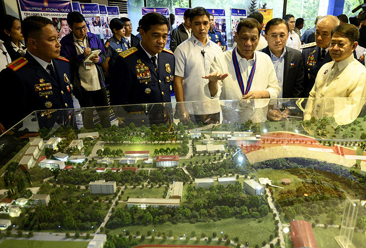 Philippine President Rodrigo Duterte (C) gestures as he looks at the diorama of the new Philippine National Police Academy during the 118th anniversary of the service, at the Camp Crame headquarters in Manila on August 9, 2019. A radio journalist was killed in the central Philippines on November 7, 2019. (AFP/Noel Celis)