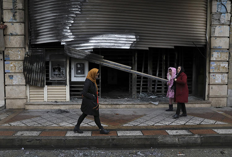 People walk past a building that was burned during recent protests in Shahriar, Iran, on November 20, 2019. Journalist Mohammad Mosaed was recently arrested after tweeting during an internet shutdown imposed amid the protests. (AP/Vahid Salemi)