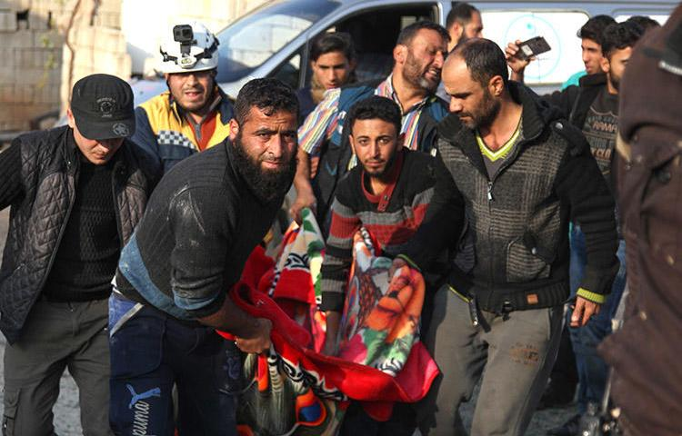 Residents and a rescue worker carry the body of a man killed in an airstrike in Kfar Rumah, in Syria's Idlib province, on November 10, 2019. A journalist for the Kafr Rumah Media Office was killed during shelling in the town. (AFP/Abdulaziz Ketaz)
