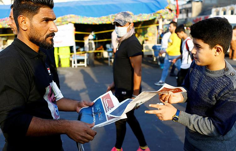 A demonstrator distributes a newspaper in Baghdad, Iraq, on November 17, 2019. A journalist was recently abducted and a broadcaster's office attacked amid the demonstrations. (Reuters/Thaier al-Sudani)