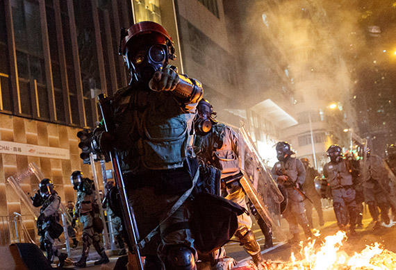 Police in riot gear pass a burning barricade in Hong Kong on November 2, 2019. Journalists covering the unrest are at risk of injury as police and protesters clash. (Reuters/Thomas Peter)