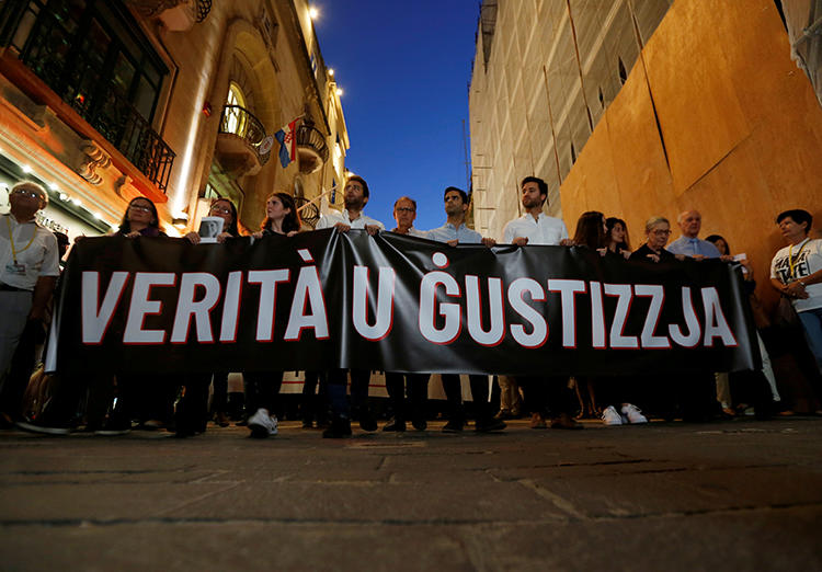 """Friends and family members of journalist Daphne Caruana Galizia carry a banner calling for """"Truth and Justice"""" in the investigation into her murder, in Valletta, Malta, on October 16, 2019. Her family and the Maltese government recently reached an agreement on the nature of the investigation. (Reuters/Darrin Zammit Lupi)"""