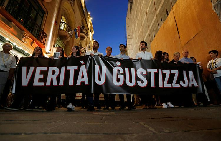 "Friends and family members of journalist Daphne Caruana Galizia carry a banner calling for ""Truth and Justice"" in the investigation into her murder, in Valletta, Malta, on October 16, 2019. Her family and the Maltese government recently reached an agreement on the nature of the investigation. (Reuters/Darrin Zammit Lupi)"
