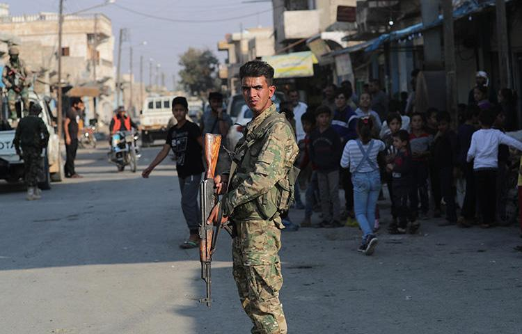 A Turkey-backed Syrian rebel fighter stands in a street in the border town of Tal Abyad, in Syria, on October 27, 2019. Military action in Syria has increased risks for journalists. (Reuters/Khalil Ashawi)