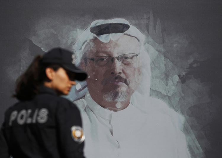 A police officer walks past a picture of Saudi journalist Jamal Khashoggi on October 2, 2019, prior to a ceremony near the Saudi consulate in Istanbul to mark the one-year anniversary of his murder. His killing and the Maguindanao massacre are emblematic of the impunity that characterizes nearly all journalist killings. (AP/Lefteris Pitarakis)