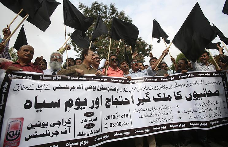 """Pakistani journalists protest censorship, holding a banner that reads: """"nation wide protest of journalists,"""" in Karachi, Pakistan, Tuesday, July 16, 2019. Pakistani journalists hold nationwide protests to denounce rampant censorship by the country's powerful security services, massive layoffs due to budget cuts and months-long delays in payments of their wages. (AP Photo/Fareed Khan)"""
