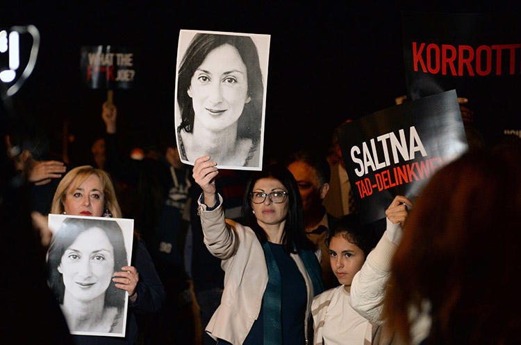 Protesters hold pictures of murdered Maltese journalist Daphne Caruana Galizia as they gather outside the prime minister's office in Valletta, Malta, on November 20, 2019. (AFP/Matthew Mirabelli)