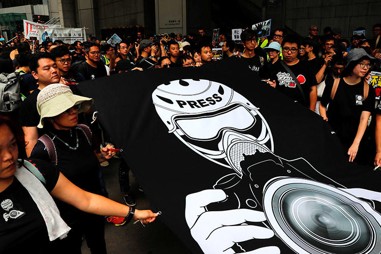 Journalists and press freedom supporters stage a silent march to police headquarters to denounce treatment of the media during protests over a proposed extradition bill, in Hong Kong, on July 14, 2019. (Reuters/Tyrone Siu)