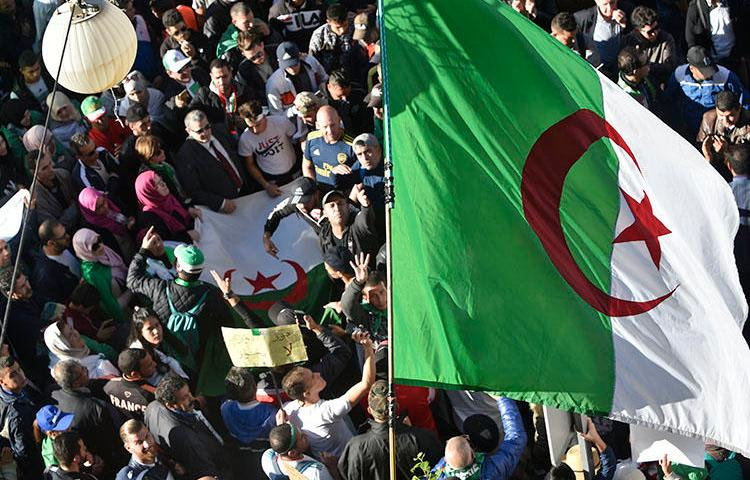 Protesters wave national flags as they gather for a demonstration against the government and the ruling class in Algiers on November 29, 2019. Algerians are due to vote in a presidential election on December 12. (AFP/Ryad Kramdi)