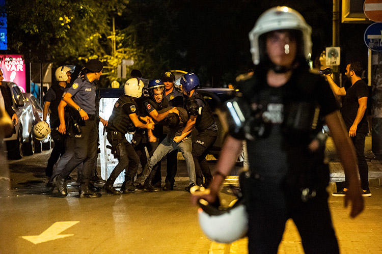 A man films as police detain a protester during a demonstration in Istanbul against the replacement of Kurdish mayors with state officials in three cities, on August 20. CPJ spoke with six journalists about the challenges of reporting and covering news in Turkey. (AFP/Yasin Akgul)